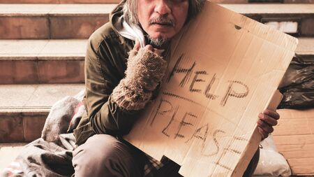 Homeless man sitting on stairs.