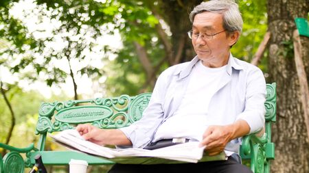 Happy asian man sitting on a bench and reading a newspaper at the park. 写真素材