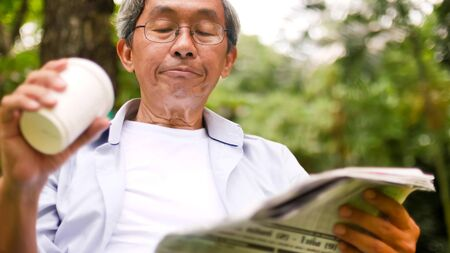 Asian man drinking coffee and reading newspaper at the park. 写真素材