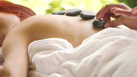 Massage therapist doing hot stone massage for woman at spa.