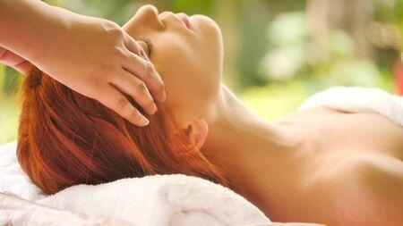 Beautiful caucasian woman getting head massage at spa.