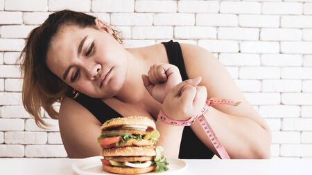 Chubby woman prohibit herself to eat hamburger.
