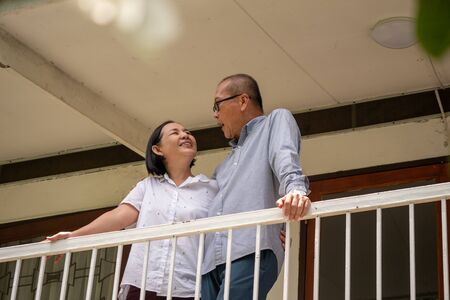 Happy asian couples standing at the balcony and talking together.