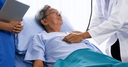 Doctor doing medical checkup for adult patient at hospital room.