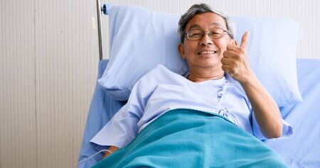 Male patient smiling and lying down on sickbed in hospital room. Stock Photo