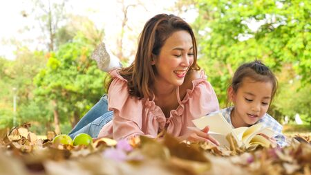 Happy asian daughter and mother reading book together at park.