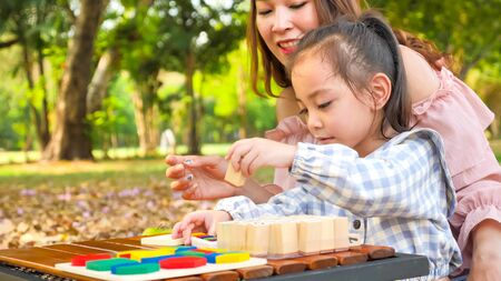 Happy asian daughter and mother playing together at park. Stock fotó
