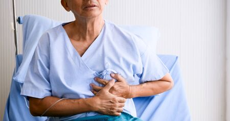 Male patient hasing chest pain on sickbed at hospital room. Stock Photo