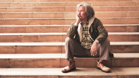 Unhappy man sitting on stairs.