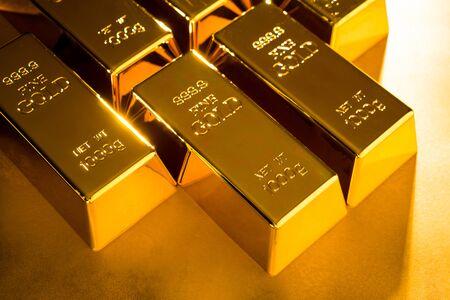 Shiny fine gold bullions on a gold background.