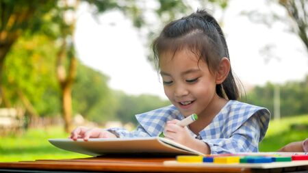 Happy girl drawing at park. 写真素材