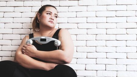 Beautiful chubby woman holding a weighing apparatus and sitting in a room.