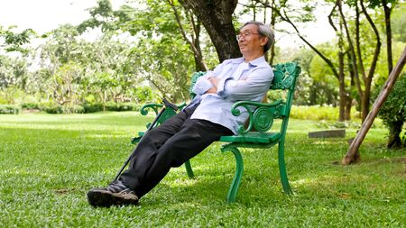 Happy asian man sitting on a bench at the park. 写真素材