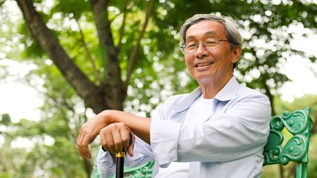 Happy asian man sitting on a bench at the park. Stock fotó