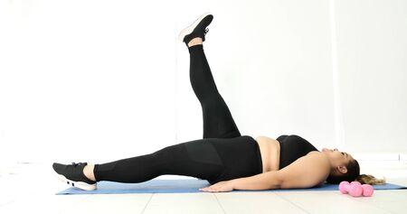 Donna paffuta che fa stretching in una stanza.