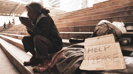 Homeless man sitting on stairs and eating food.