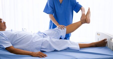 Physical therapist doing physical therapy for adult patient at hospital room. Archivio Fotografico - 136183109