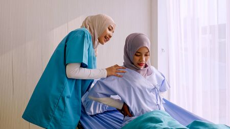 Muslim female physiotherapist taking care of patient at hospital room.