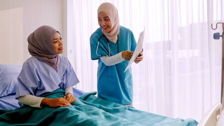 Muslim female doctor analysing disease to patient at hospital room. Stock Photo