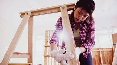 Female carpenter screwing pieces of boards together at site.