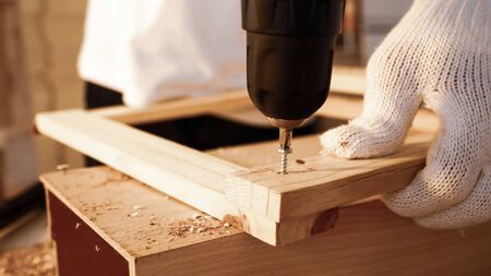 Close up of carpenter using drill to screwing pieces of board at site.