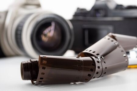 Single lens reflex cameras and a film roll on a white background.