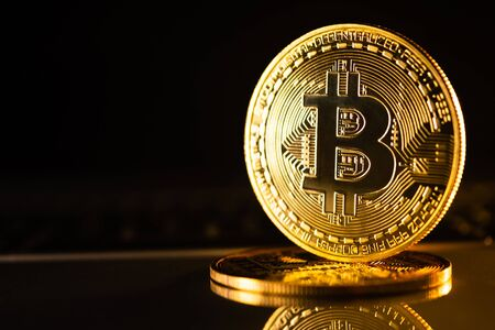 Golden coins with bitcoin symbol on a black background. Stock Photo