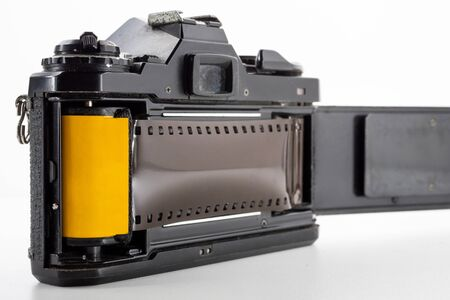 Single lens reflex camera and a film roll on a white background. Stockfoto