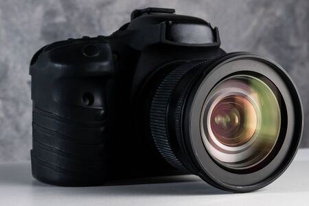 Black digital camera on a table with grunge background. 免版税图像