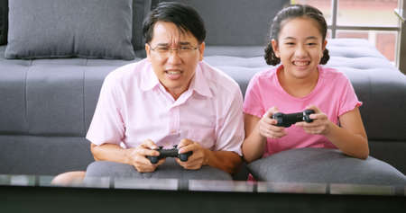 Father and daughter wear protective masks and keep the social distance while working at home.