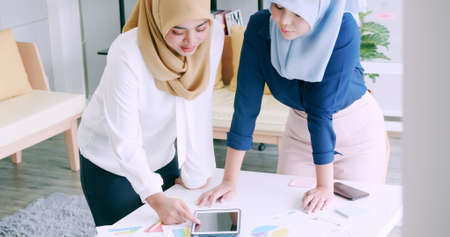 Muslim businesswomen wear protective masks and clean hands with sanitizer alcohol gel during work in office.