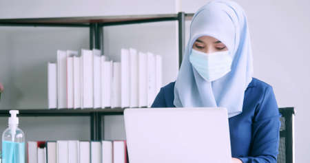 Muslim businesswoman wear protective masks during work in office.
