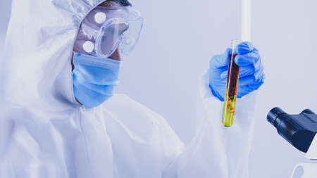 Scientist in PPE suite doing some research checking a liquid in a test tube at laboratory.