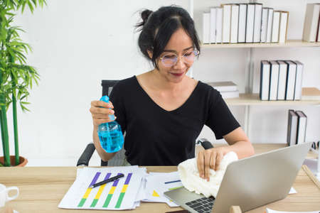 Young woman cleaning the surface of laptop with alcohol spray and fabric at home Stockfoto