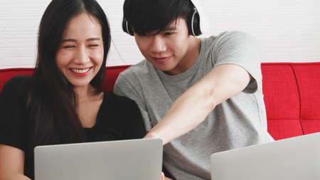 Happy Asian couple   sitting working together on sofa at home.
