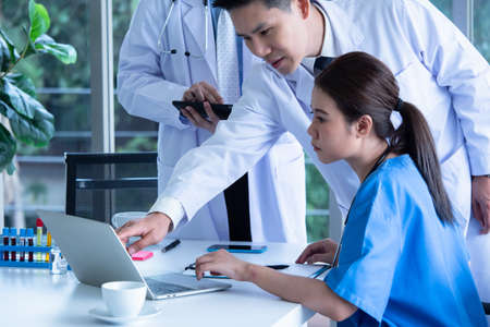 Doctor and medical assistants discussing about diagnosis result on laptop. Stockfoto