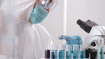 Asian scientist doing some research and looking through a microscope in laboratory. Stockfoto