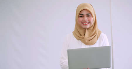 Portrait of young Asian Muslim business woman with laptop.