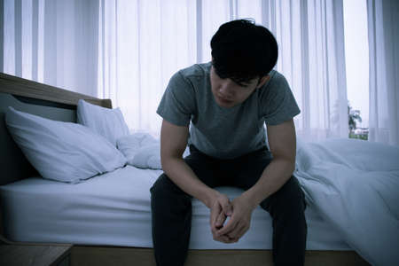Stressed Asian young man sitting alone on bed. Bad relationship or bankrupt problem and sickness concept. 스톡 콘텐츠