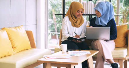 Two young Muslim businesswomen discussing a work in the office.