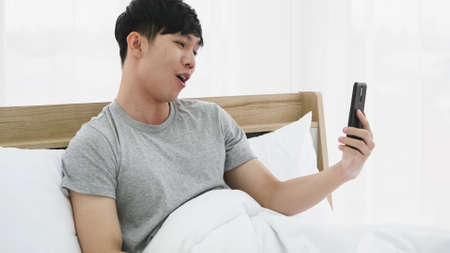 Young happy man using mobile phone for video call in bed at home