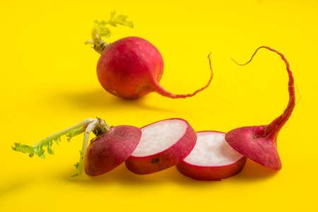 Red ripe sliced radish on yellow background Foto de archivo