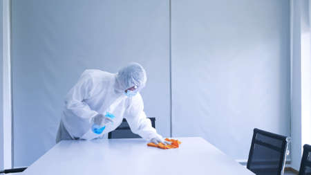 Worker in personal protective equipment (ppe) suit cleaning in building with spray disinfectant water to remove covid 19