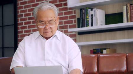 Eldery man using laptop computer at home.
