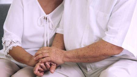Close up of eldery couple holding hands together. Foto de archivo