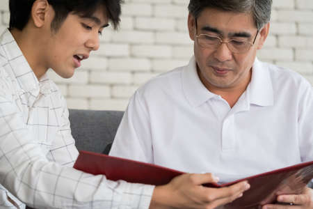 Young man agent recommending life insurance to senior man.