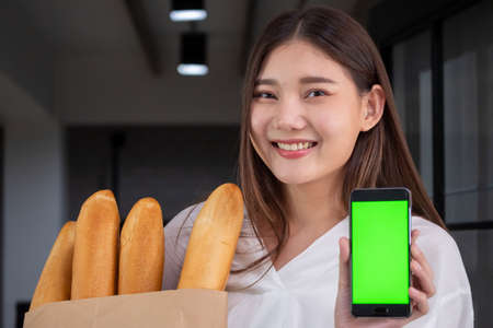 Happy woman holding fresh baked bread and smartphone, Food delivery concept