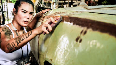 Attractive young woman mechanical worker repairing a vintage car in old garage.