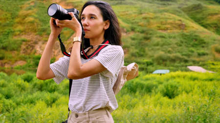 Young woman taking photos of natural view.
