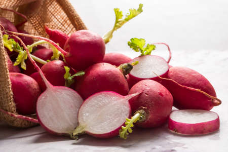 Close up of red ripe sliced radishes in a basket with grunge background